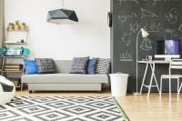 Sivá pohovka s dekoračnými vankúšmi a pracovný kút v študentskej izbe