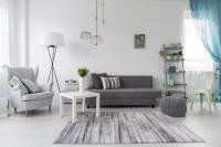 Sivá pohovka a kreslo ušiak vo svetlej obývačke