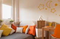 Biela posteľ s dekoračnými vankúšmi a oranžové samolepky na stenu