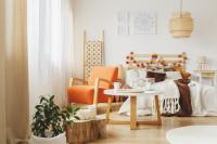Oranžové kreslo a drevená posteľ v boho spálni