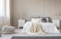 Manželská posteľ a drevené nočné stolíky vo svetlej romantickej spálni