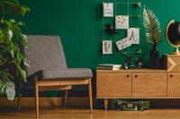 Sivé retro kreslo a komoda v kontraste so zelenou stenou