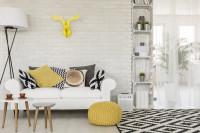 Biela pohovka s dekoračnými vankúšmi a žltým pufom
