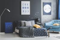 Manželská posteľ v tmavej spálni v modrých tónoch