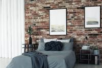 Manželská posteľ so sivou posteľnou bielizňou v industriálnej spálni s tehlovou stenou