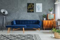 Modrá pohovka a lavica v retro obývačke so sivou stenou
