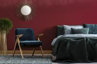Modré kreslo a posteľ v bordovej glamour spálni