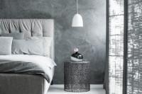 Manželská posteľ s čalúneným čelom a okrúhly odkladací stolík v spálni v sivých tónoch
