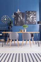 Sivé retro stoličky a drevený stôl v jedálni s modrou stenou
