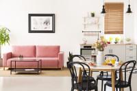 Ružová pohovka a čierne stoličky v škandinávskej obývačke