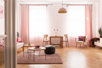 Retro nábytok v priestrannej obývačke s ružovými závesmi