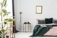 Kovový stolík a veľká posteľ s vankúšmi a sivou dekou