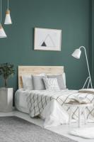 Posteľ s bielymi obliečkami v spálni so zelenou stenou