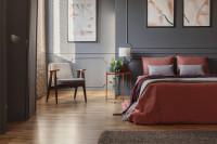 Manželská posteľ v tehlových tónoch v sivej spálni