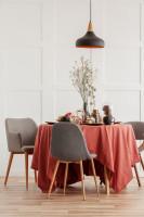Okrúhly jedálenský stôl s červeným obrusom a jesennou dekoráciou zo suchých kvetov