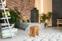 Manželská posteľ a kovová skriňa v spálni s tehlovou stenou