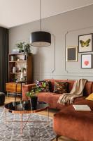 Hnedá rohová pohovka a okrúhly medený stolík