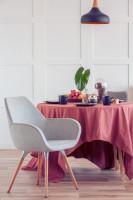 Sivé kreslo s podrúčkami a okrúhly jedálenský stôl