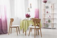 Drevené stoličky a okrúhly stôl vo vzdušnej bielej jedálni