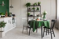 Okrúhly jedálenský stôl so zeleným obrusom a drevené stoličky