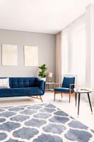 Modrá pohovka a retro kreslo vo svetlej obývačke