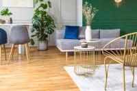 Sivá pohovka a sada zlatých okrúhlych stolíkov