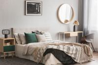 Manželská posteľ vo svetlej spálni s okrúhlym zrkadlom