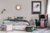 Veľká manželská posteľ a kreslo ušiak vo svetlej glamour spálni