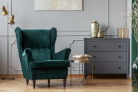 Zelené kreslo ušiak v sivej klasickej obývačke