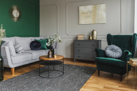 Kreslo ušiak a okrúhly stolík v zeleno-bielej obývačke