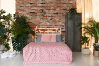 Manželská posteľ s ružovou dekou v industriálnej spálni