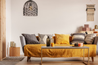 Pohovka s dekoračnými vankúšmi a žltými doplnkami