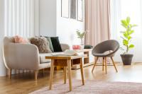 Svetlá pohovka a sivé kresielko vo vzdušnej obývačke