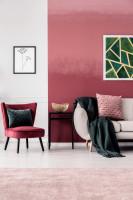 Bordové kreslo a biela pohovka v obývačke s ružovou stenou
