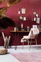 Kovová stolička s dekou a písací stôl v bordovej pracovni