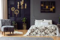 Manželská posteľ v sivej glamour spálni so zlatými doplnkami