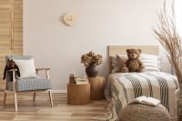 Drevená posteľ a kreslo v detskej izbe v neutrálnych farbách