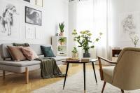 Čierny stolík a svetlá pohovka s dekoračnými vankúšmi