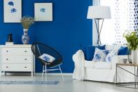 Biela pohovka a komoda v obývačke s výraznou modrou stenou