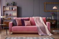 Ružová pohovka s dekoračnými vankúšmi v glamour obývačke so sivou stenou