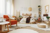 Drevená manželská posteľ a čalúnené kreslo v priestrannej spálni
