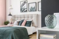 Manželská posteľ s čalúneným čelom v sivo-bielej spálni