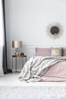 Manželská posteľ s ružovými obliečkami a kovové doplnky