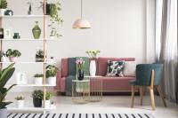 Malé kreslo a ružová pohovka v romantickej obývačke