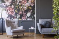 Sivé kreslo ušiak v glamour obývačke s výraznou tapetou s motívom kvetov