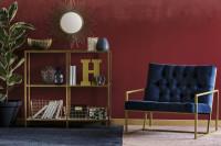 Modré kreslo a zlaté doplnky v bordovej glamour obývačke