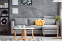Rohová pohovka so žltým vankúšom v sivej obývačke