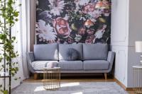 Sivá pohovka v kontraste s tapetou s výrazným motívom kvetov