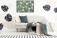 Biela pohovka s pletenými dekami a motívom listov