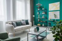 Svetlá pohovka v obývačke s výraznou zelenou stenou